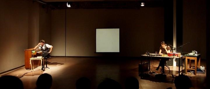 Bühnenfoto, links und rechts außen die sitzenden Darsteller