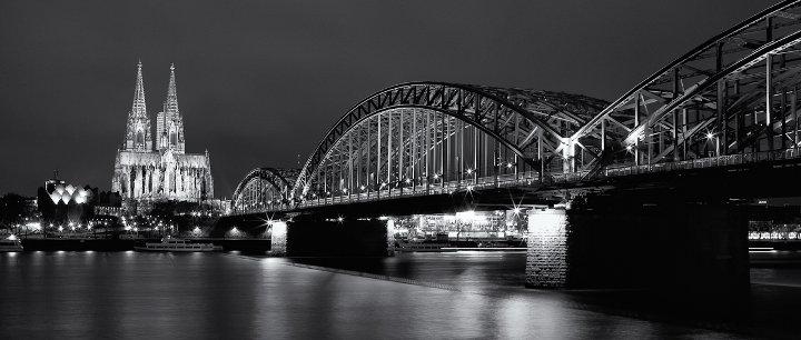Die Kölner Hohenzollernbrücke bei Nacht in schwarz-weiß